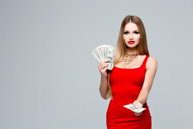 Ritratto di giovane donna affascinante in abito rosso con trucco luminoso, labbra rosse, una collana d'oro. la donna tiene in mano molti soldi, con l'altra mano ti dà soldi.