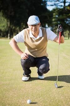 Ritratto del giocatore di golf che si accovaccia e che guarda la sua palla