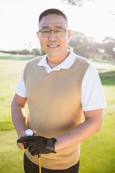 Ritratto del giocatore di golf che posa con una palla