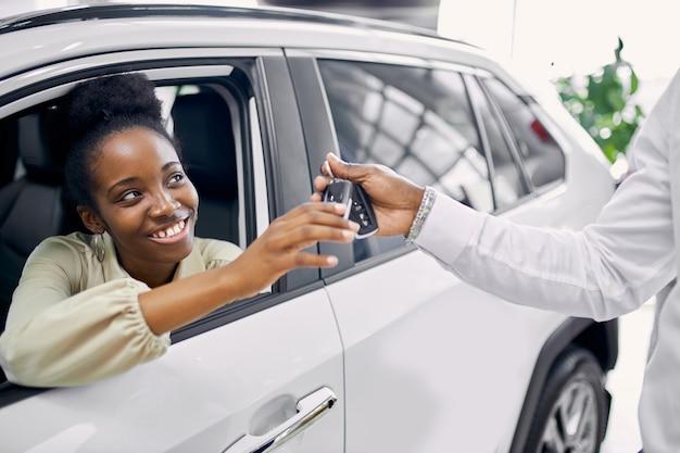 Ritratto di bella signora afro che ottiene le chiavi in macchina
