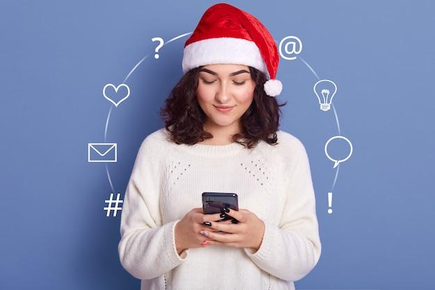 Ritratto di bella giovane mora che indossa un maglione bianco, cappello di babbo natale rosso, con smartphone in entrambe le mani