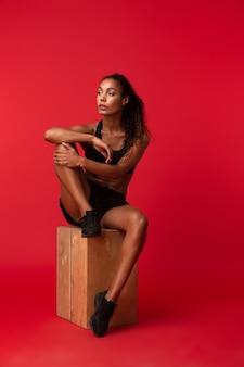 Ritratto di splendida donna afro-americana in abiti sportivi neri che si siede sulla scatola, isolata sopra la parete rossa