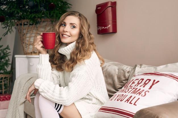Ritratto di donna bionda splendida in maglione di lana bianco che beve caffè caldo in interni decorati accoglienti leggeri