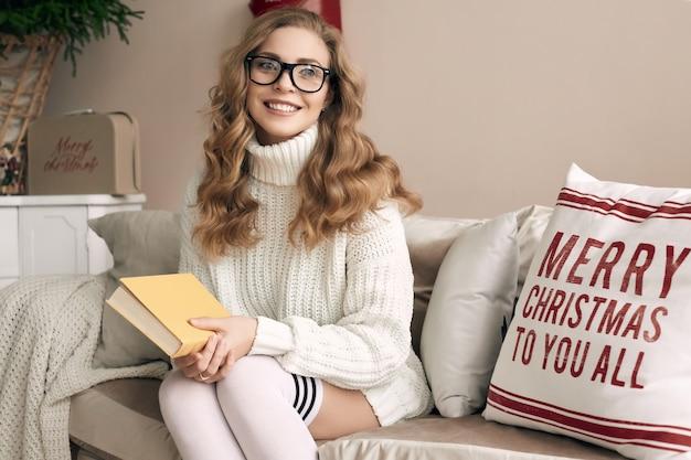 Ritratto di donna bionda splendida in maglione di lana bianco e occhiali da lettura libro in interni decorati luminosi accoglienti