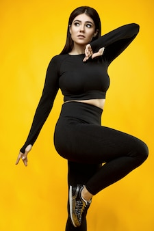 Ritratto di una donna latina positiva del corpo splendido in un vestito di sport nero che si esercita sul giallo