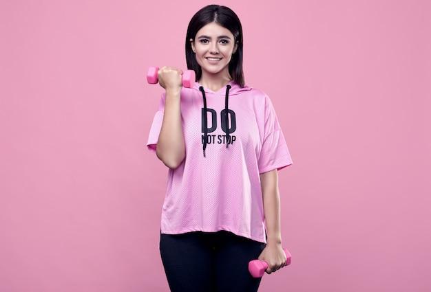 Ritratto di una donna latina positiva del corpo splendido in una felpa con cappuccio rosa di sport che si esercita con le teste di legno sul rosa