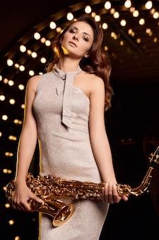 Ritratto di donna bellissima modella bruna in abito elegante con il sassofono che gioca sui riflettori del palcoscenico del ristorante.