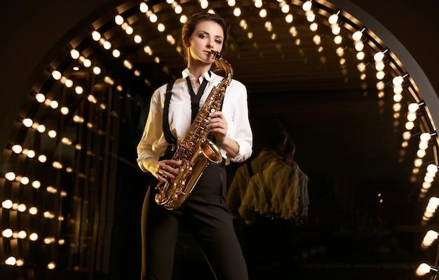 Ritratto di donna bellissima modella bruna in abito formale alla moda con il sassofono