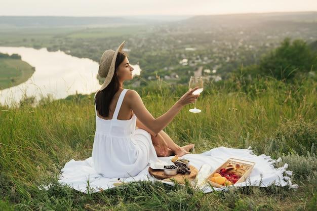 Ritratto di splendida donna bruna in abito bianco e cappello di paglia con vino sulla collina con un bellissimo paesaggio