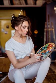 Ritratto di una splendida artista femminile che lavora a diversi progetti artistici nel suo studio.
