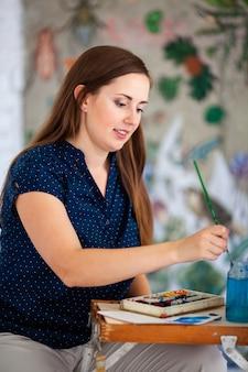 Ritratto di una splendida artista femminile che lavora su diversi progetti artistici nel suo studio