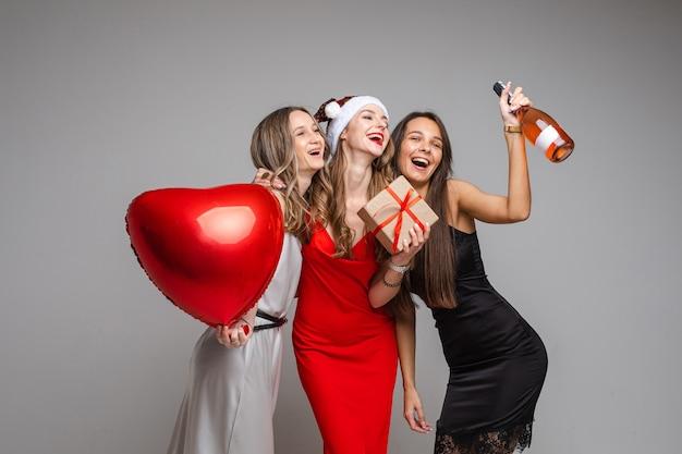 Ritratto di splendide donne felici in abiti di seta con mongolfiera a cuore rosso, regalo e bottiglia di vino rosato divertendosi abbracciando e posando sul muro grigio