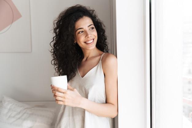 Ritratto di splendida donna felice con lunghi capelli ricci che osserva da parte attraverso la finestra mattina a casa e tenendo la tazza di tè
