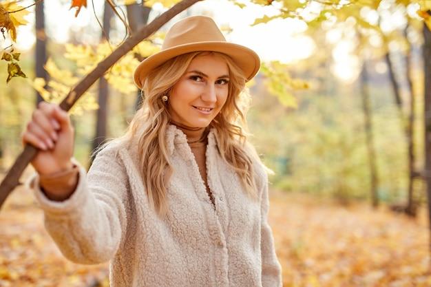 Ritratto di splendida signora in cappello che propone alla macchina fotografica nella natura di autunno
