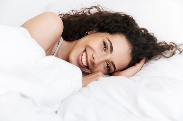Ritratto di splendida donna anni '20 con capelli ricci scuri sdraiata a letto su lino bianco e sorridente