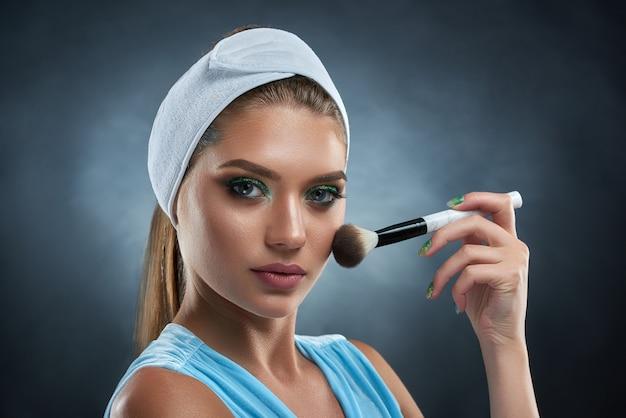 Ritratto di donna splendida che indossa in blu con benda sulla testa