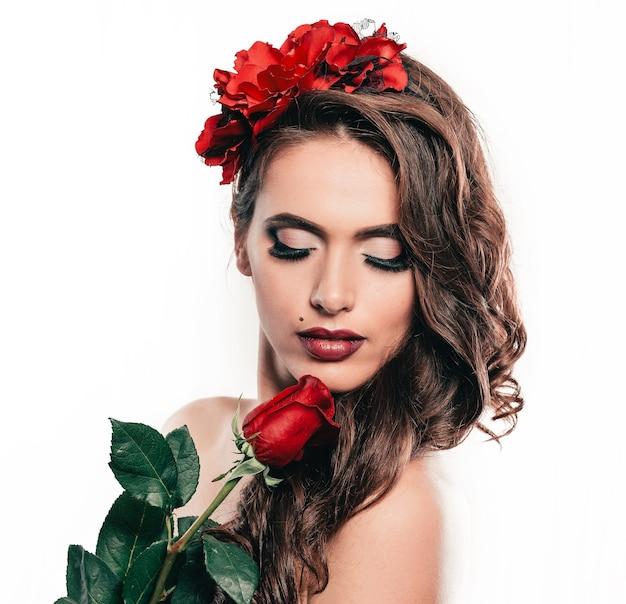 Ritratto di una splendida donna con una rosa rossa.