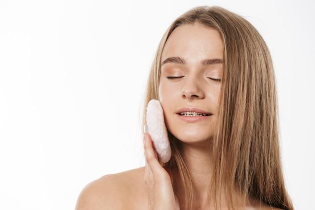 Ritratto di splendida giovane bionda donna mezza nuda che applica il trucco con una spugna in polvere isolata su bianco