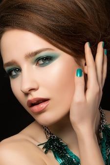 Ritratto di splendida giovane donna con unghie blu e trucco degli occhi che tocca i suoi capelli