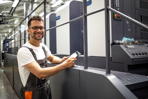 Ritratto di ingegnere grafico in piedi vicino alla moderna macchina da stampa offset che controlla il processo di stampa