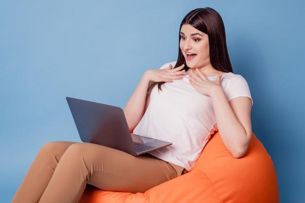 Ritratto di grata felice bella signora sit beanbag tenere le mani del computer petto su sfondo blu