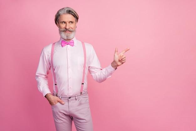 Ritratto di uomo dai capelli grigi che mostra il lato di sguardo dell'annuncio di consiglio della soluzione sulla parete rosa