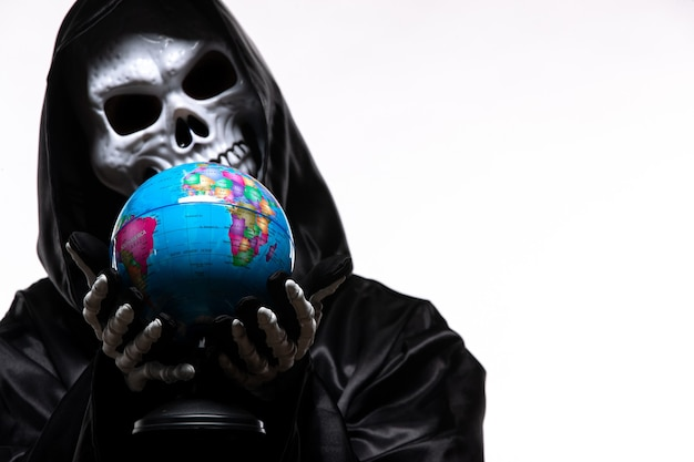 Ritratto di grim reaper in abiti neri con piccolo globo su bianco