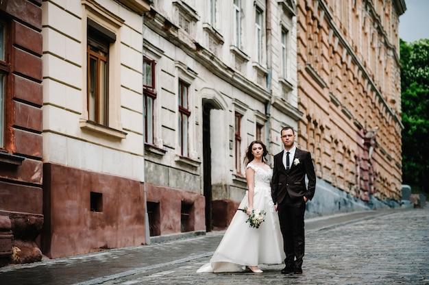 Ritratto lo sposo e la sposa stanno vicino al vecchio edificio all'aperto. sposi per le strade della città.