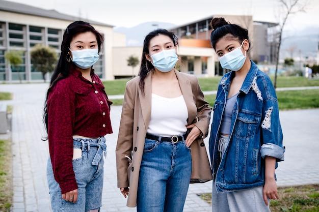 Ritratto di un gruppo di amiche asiatiche utilizzando una maschera per il viso mentre in piedi all'aperto