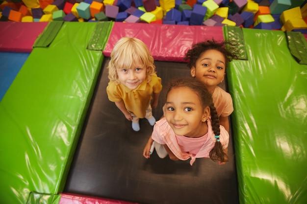 Ritratto di un gruppo di bambini che guardano davanti mentre salta sul trampolino nel parco dei divertimenti