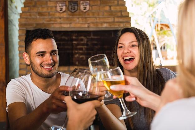 Ritratto di un gruppo di amici seduti in un ristorante per condividere un pasto e brindare insieme ai loro bicchieri