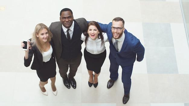 Ritratto di un gruppo di uomini d'affari felici e diversi che stanno insieme. saltano in aria e fanno il tifo per festeggiare il successo dell'azienda.