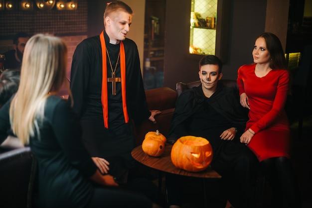 Ritratto di gruppo di giovani in colorati costumi di halloween seduti e chiacchierare in un accogliente caffè. zucca intagliata sul tavolo.