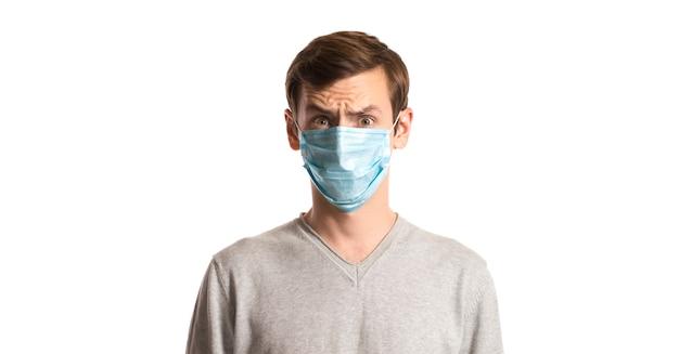 Ritratto di un ragazzo in una maschera usa e getta su un bianco