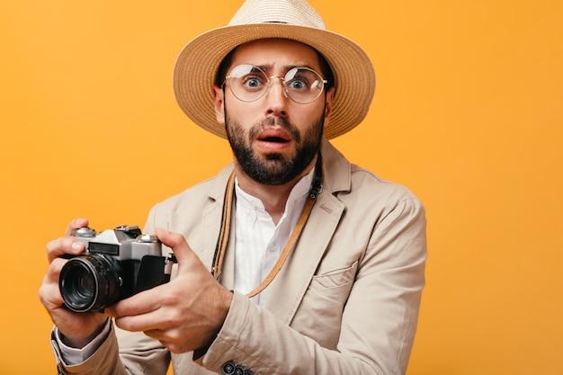 Ritratto di ragazzo in cappello e occhiali confuso in posa sul muro arancione con fotocamera retrò