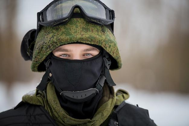 Ritratto di un ragazzo con un elmetto militare, una maschera e un komflag