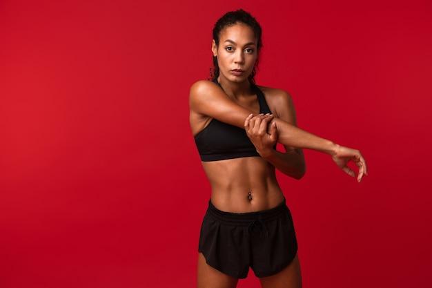 Ritratto di donna afroamericana ginnastica in abiti sportivi neri che allunga il suo corpo, isolato sopra la parete rossa