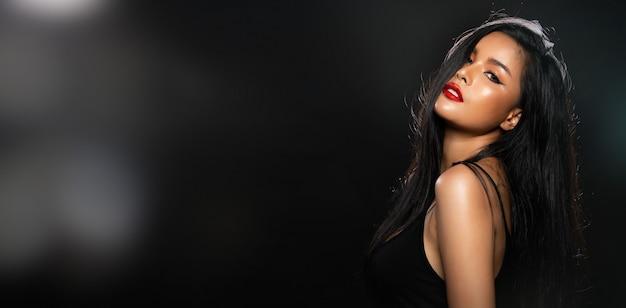 Mezzo corpo del ritratto di donna asiatica in stile vasto nero di alta moda su sfondo di nebbia di fumo con illuminazione retroilluminata dal retro, bandiera dello spazio della copia