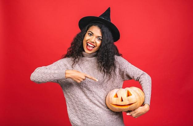 Ritratto della donna afroamericana della strega di halloween che tiene una zucca