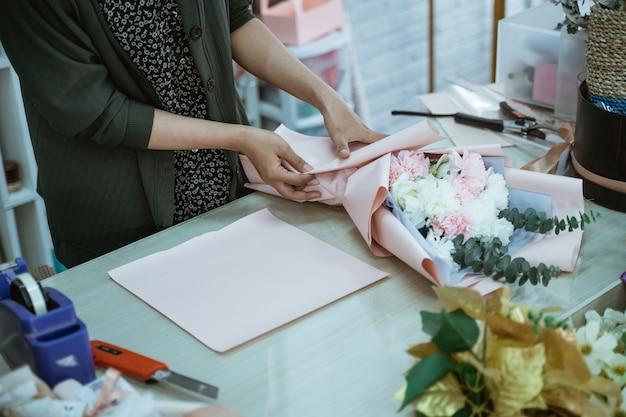 Il fiorista della mano del ritratto fa un artigianato di fiori di flanella sul tavolo