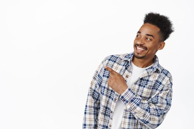Ritratto di bel ragazzo afroamericano che sorride felice, indicando e guardando a sinistra il banner promozionale di vendita, mostrando pubblicità, in piedi in abiti casual su bianco.
