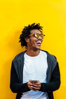 Ritratto di un bell'uomo afro che usa il cellulare per strada.