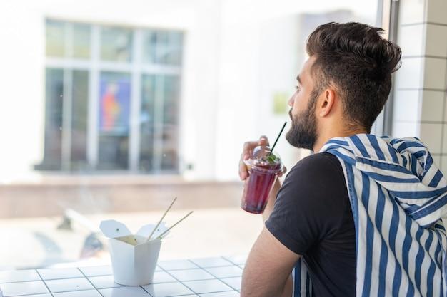 Ritratto di un bell'uomo arabo che beve frullato in un caffè. il concetto di bevande salutari e stile di vita.