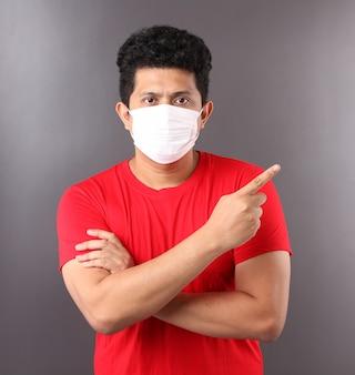 Il ritratto dell'uomo asiatico bello che indossa una maschera è malato che indica il dito