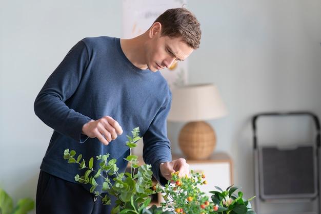 Ritratto del giardiniere del giovane ragazzo attraente bello prendersi cura dei piani di innaffiarli a casa