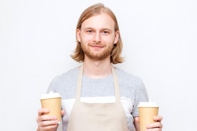 Ritratto di un bel barista in maglietta grigia e grembiule che tiene due bicchieri di carta. uomo barista hipster con barba e acconciatura lunga
