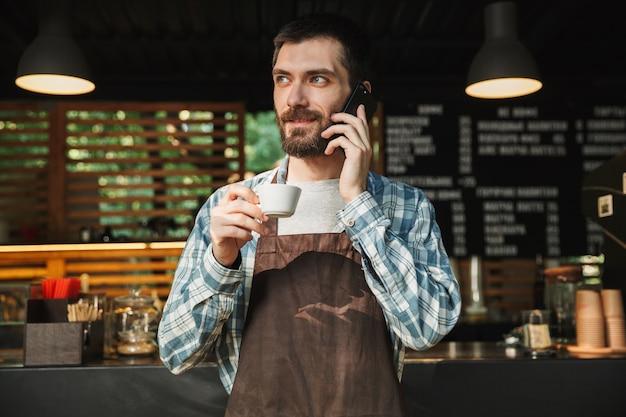 Ritratto di un bel barista che indossa un grembiule che beve caffè e parla al cellulare in un caffè di strada o in un caffè all'aperto