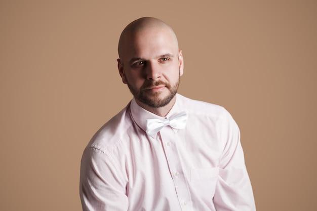 Ritratto di uomo calvo barbuto bello in camicia rosa chiaro e fiocco bianco, seduto su una sedia e guardando lontano e sorridente. girato in studio al coperto, isolato su sfondo marrone.