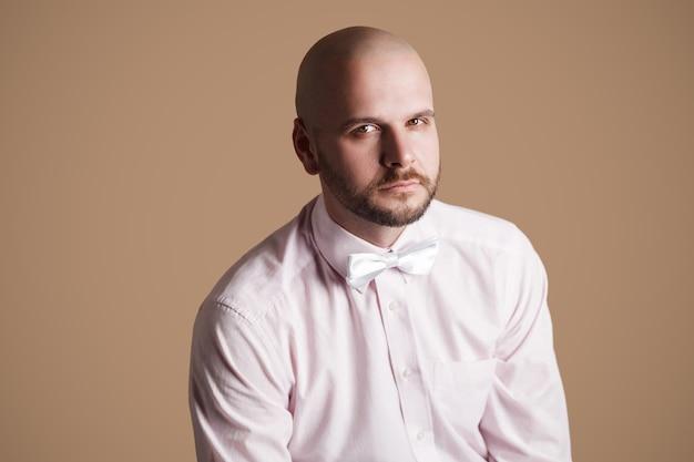 Ritratto di uomo calvo barbuto bello in camicia rosa chiaro e fiocco bianco, seduto su una sedia e guardando la telecamera con la faccia seria. girato in studio al coperto, isolato su sfondo marrone.
