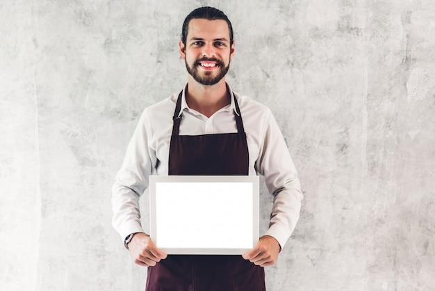 Ritratto del barista barbuto bello uomo piccolo imprenditore sorridente e in possesso di bordo di legno vuota cornice con mockup bianco vuoto in un caffè